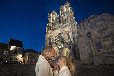 Photo d'un couple s'embrassant de nuit au pied de la cathédrale